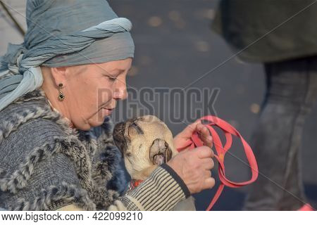 An Adult Woman Talking To Her Pet At The Fall All-breed Dog Show. The Owner Is Holding A Red Leash A