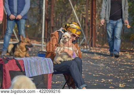 Happy Adult Woman Wearing A Scarf And Glasses Brushes Her Pet At The Fall All-breed Dog Show. A Smil