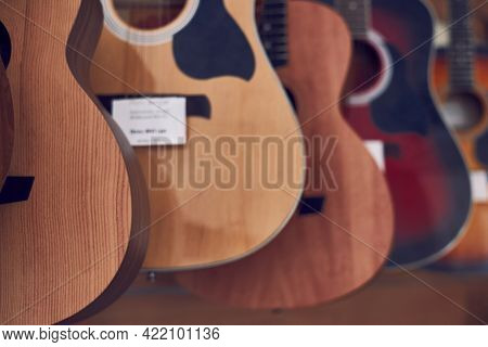 A Range Of New Acoustic Guitars In A Store, Close-up.