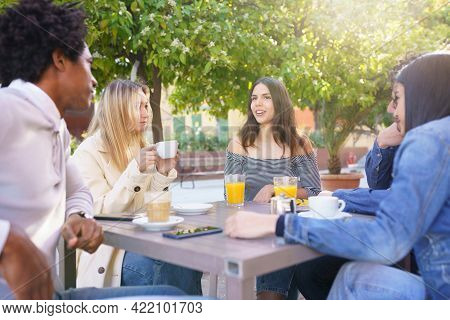 Multi-ethnic Group Of Students Having A Drink On The Terrace Of A Street Bar.