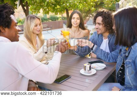 Multi-ethnic Group Of Friends Toasting With Their Drinks While Having A Drink Together.