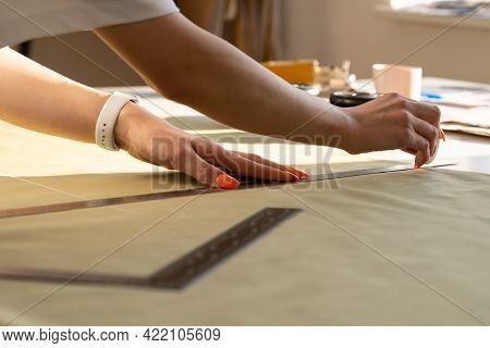 Creating Clothes Concept: Unrecognizable Female Seamstress Work With Draft And Fabric On Sewing Tabl