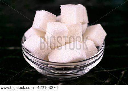 Sugar In A Glass Bowl On A Black Background. Refined Sugar.