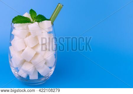 A Glass Full Of Sugar On A Blue Background. The Concept Of Harmful Sweet Carbonated Drinks.