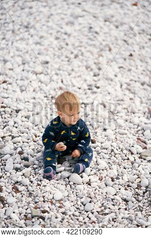 Cute Kid In Blue Overalls Sits On A Pebble Beach And Holds A Pebble In His Hand