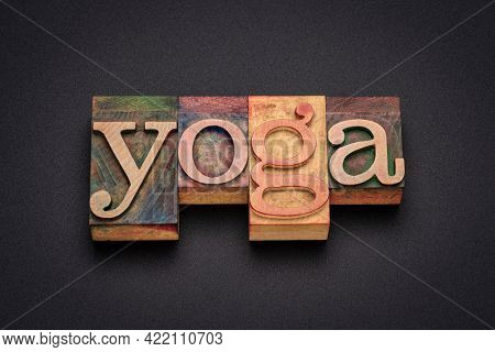 yoga word - text in letterpress wood type printing blocks stained by color inks against black background