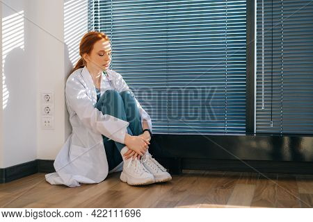 Frustrated Young Female Doctor In White Coat Sitting On Floor Near Window With Louvre In Dark Medica
