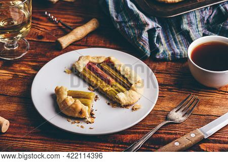Rhubarb Mini Galette On White Plate With Glass Of Wine And Cup Of Coffee