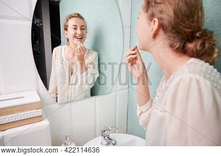 Young Woman Using Elastic Cleaning Toothpick While Brushing Teeth With Orthodontic Brackets. Joyful