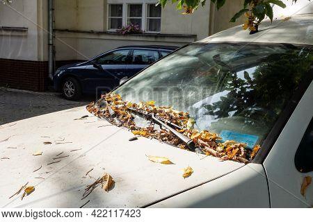 Karvina, Czech Republic - September 13, 2020: The Abandoned White Wreck Car Covered By Fallen Leaves