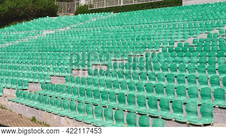 Lots Of Empty Seats In Old Open-air Theater Theater. Plastic Green Seats Are Arranged In A Rows.