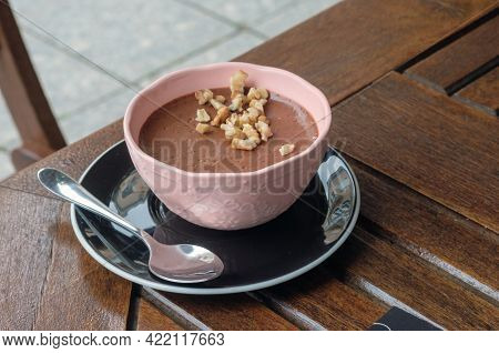 A Pink Bowl With Chocolate Mousse, Pieces Of Walnut And A Teaspoon On The Dark Brown Table At Cafe