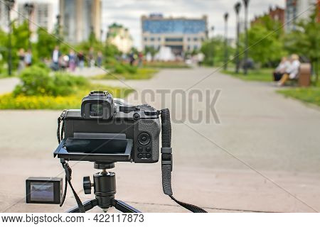 The Camera And The Action Camera Stand On The Road, On The Platform, On A Tripod In The City Park An