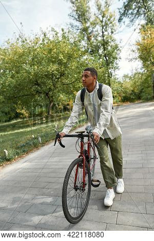 Happy Young African American Man With Backpack Walking With Bike Along Park Alley In Spring Nature,