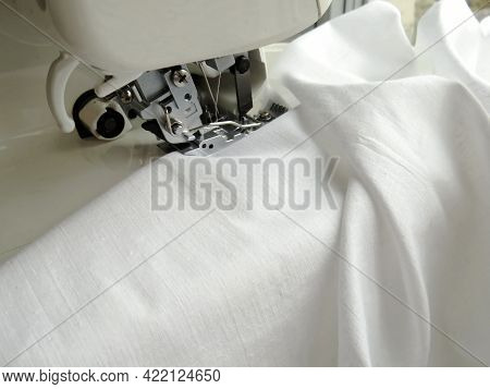The Sewing Machine Is Sewing White Fabric. Overlock Fabric Edges. Garment Industry