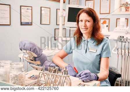 Dentist In Sterile Gloves Looking At Camera While Holding Marker Pen. Woman Orthodontist Sitting At
