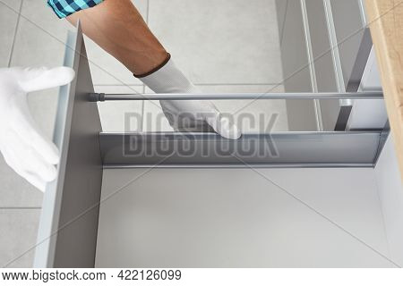 Handyman Assembling And Sets Up A Drawer In The Kitchen. Worker Fix The Furniture Mechanism Of The C