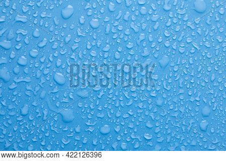 Water Drops On Blue Background. Drops Of Water On Surface. Macro Photo. Splash Pattern.