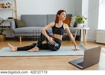 Young Fit Woman With Laptop Watching Online Video Lessons And Practicing Yoga At Home. Fitness Exerc