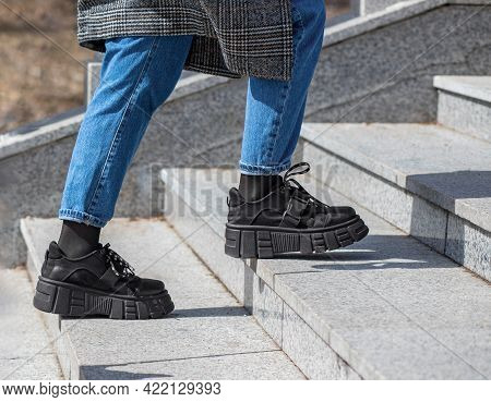 A Girl In Massive Black Boots, Jeans And A Checkered Coat Climbs Up The Granite Stairs. Front View