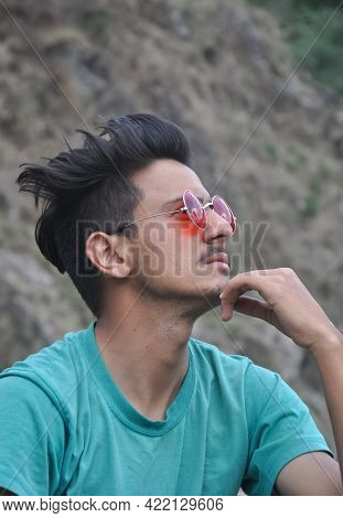 Closeup Shot Of A Good Looking Young Guy Wearing Sunglass Sitting Outdoor And His Hand On Chin With