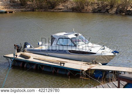 A Small Motor Boat Stands At A Wooden Pier On A Lake On A Summer Day. Top View