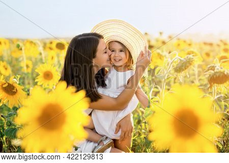 A Mother Lovingly Hugs And Kisses Her Daughter At Sunset In A Field Of Sunflowers. Happy Family. Uni
