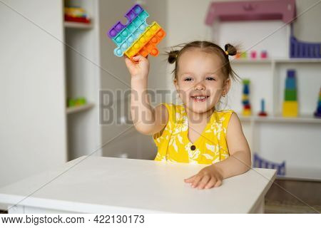 A Little Girl Is Playing At A Table With A Pop It Toy. A Fascinating Sensory Toy For Development. Co
