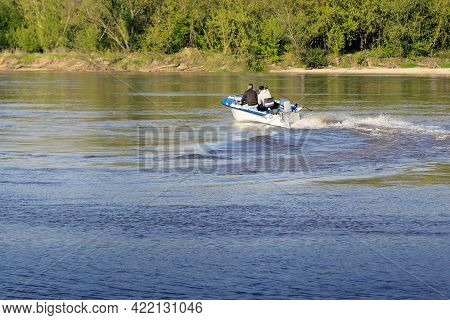 Two People Are Riding A Motorboat On The River And Making A Turn.