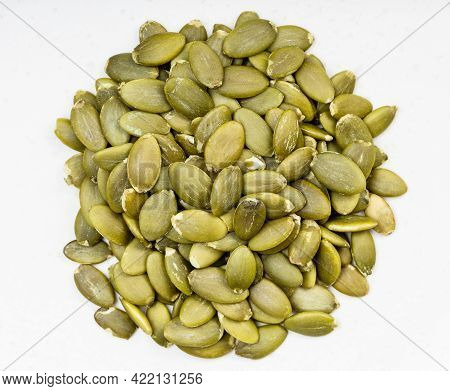 Top View Of Pile Of Hulled Pumpkin Seeds Close Up On Gray Ceramic Plate