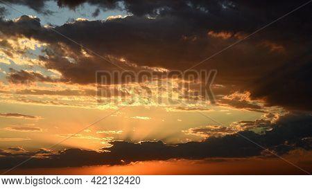 Bright Golden Sunbeams Shining Through Dark Clouds. Orange Brown Cloudscape Of Sunset. Dramatic Sky