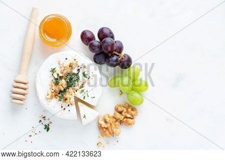 Brie Or Camembert Cheese Served With Grapes, Honey And Walnuts