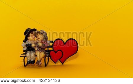 Figures Of Toys Of A Boy And A Girl On A Bench With Hearts On A Yellow Background. Declaration Of Lo