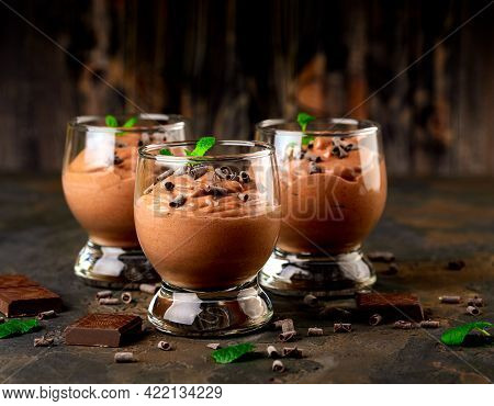 Vegan Chocolate Mousse With Mint, Bar Of Chocolate And Cocoa Beans On A Dark Background. Copy Space