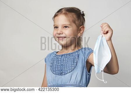 Little Girl Wearing Face Mask. Child Girl With Medical Mask, Close-up Portrait On A White Background