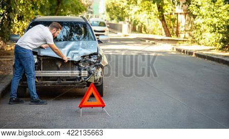 Driver Man Looking On Wrecked Car In Car Accident. Man Regrets About Fixing Car Headlight After Auto