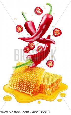 Fresh red chilli pepper and sections of chilli pepper floating over honeycombs and honey puddle isolated on white background. Clipping path.
