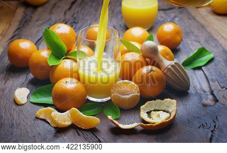 Pouring tangerine juice into the glass. Tangerine fruits and slices are near the glass on dark wooden table.