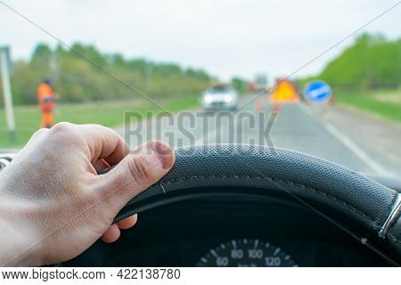 The Driver Hand On The Steering Wheel Inside The Car On The Background Of The Highway, Blocked By An