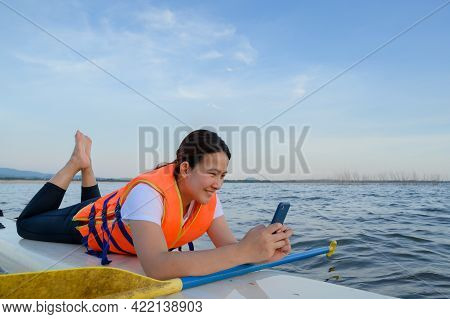 Asian Athletic Woman With Mobile Phone On Stand Paddle Board In Lake. Solo Outdoor Sup Activity On S