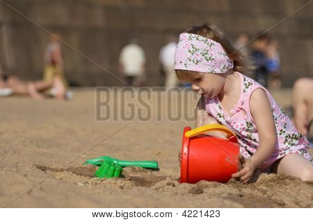 Little Girl Playing On Sand