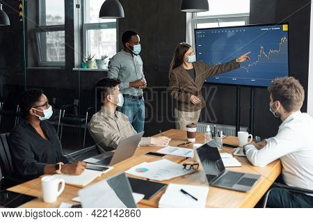 Colleagues Having Meeting In Boardroom, Businesswoman Showing Graph
