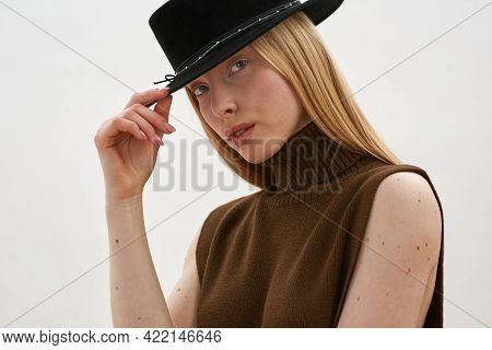 Portrait Of Tempting Young Caucasian Woman Wearing Stylish Hat While Posing On White Background And