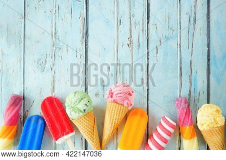 Variety Of Colorful Summer Frozen Desserts. Top View Bottom Border On A Rustic Blue Wood Background.