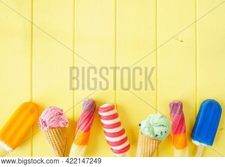 Assortment Of Colorful Summer Frozen Desserts. Top View Bottom Border On A Bright Yellow Wood Backgr