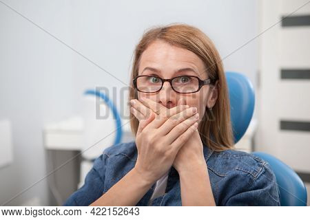Scared Woman Covering Her Mouth With Hands, Sitting In Dentists Office