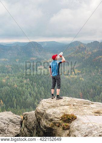 Thirsty Sportsman Drinking On Summit.  Man Achieved Personal Peak, Refreshing Body Power.