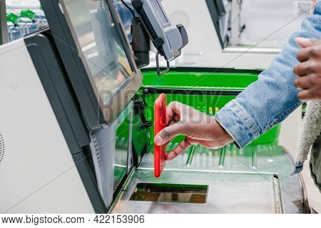 A Close-up Of An African Mans Hand Paying At A Grocery Supermarket Checkout With A Contactless Payme