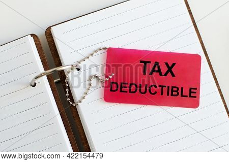 Tax Deductible Inscription On A Red Card, Which Is Attached On A Chain To A Blank Notebook On The Ta