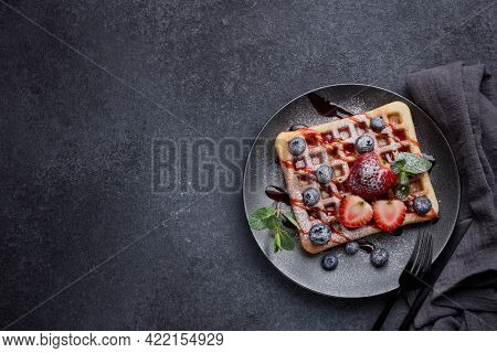 Delicious waffles with berries, mint, powdered sugar and sweet sauce on ceramic black plate on grey background. Top view with copy space. Sweet meal. Dessert. Serving food